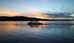 silhouette-cruising-boat-lake-titicaca-sunset-puno-peru_76000-705